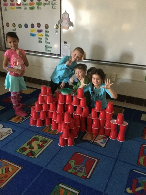 Students use 100 red cups to build a structure.