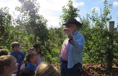 Farmer Chuck talks to student in the U-Pod about varieties of apples.