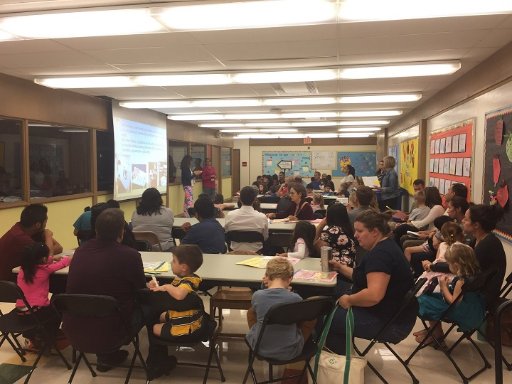 Parents and students listen to teachers explain what the students do during reading.
