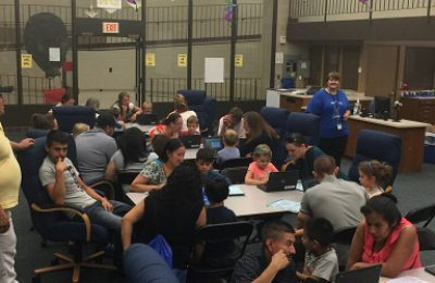 Parents and students use laptops to play computer programs provided by KCSD.