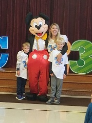 Mrs. Pudelka and her sons hug Mickey Mouse
